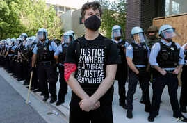A demonstrator stands in front of Chicago Police officers during the March for Justice in honor of George Floyd Saturday, June…
