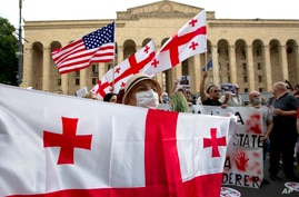 An activist wearing a face mask to protect against coronavirus holds the Georgian flag during a rally in Tbilisi, Georgia,…