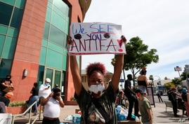A woman holds a sign addressing ANTIFA at a protest in Los Angeles on Monday, June 1, 2020, over the death of George Floyd, who…