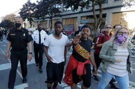 Seattle Fire Assistant Chief Willie Barrington, left, and Chief Harold Scoggins, second from left, walk with protest organizers…