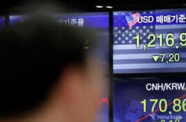 A currency trader works near the screens showing the foreign exchange rates at the foreign exchange dealing room in Seoul,…
