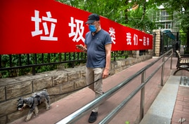 A man wearing a face mask to protect against the spread of the new coronavirus walks past a propaganda banner encouraging…
