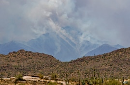 A portion of the Bush fire burns through the Tonto National Forest, Tuesday, June 16, 2020, as seen from Apache Junction, Ariz…