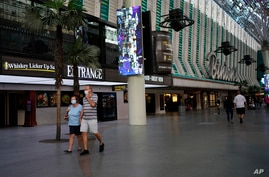 People in masks walk by Binion's casino Monday, June 15, 2020, in Las Vegas. Nevada Gov. Steve Sisolak announced Monday that…