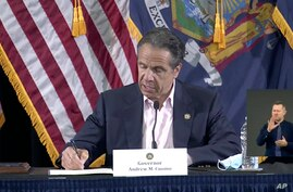 In this image made from video provided by the office of Gov. Andrew M. Cuomo, Gov. Cuomo signs a bill giving death benefits to…