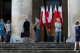 People, keeping social distancing, wait in line to cast their vote in presidential election in Warsaw, Poland, Sunday, June 28,…