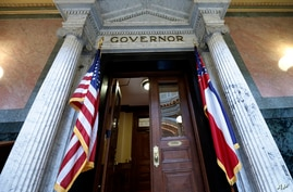 The Mississippi state flag is anchored across from the American flag, outside the Governor's Office at the Capitol in Jackson,…