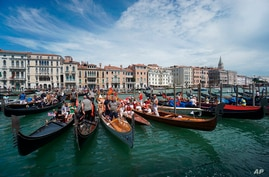 FILE - In this Sunday, June 21, 2020 file photo, gondolas are lined up during the Vogada della Rinascita (Rowing of Rebirth)…