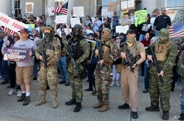 FILE - In this May 2, 2020, file photo, people, including those with the boogaloo movement, demonstrate against business…