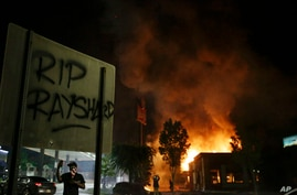"""RIP Rayshard"" is spray painted on a sign as as flames engulf a Wendy's restaurant during protests Saturday, June 13, 2020, in…"