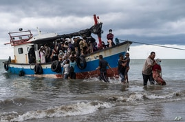 Local fisherman help ethnic-Rohingya people as they arrive on Lancok Beach, North Aceh, Indonesia, Thursday, June 25, 2020…