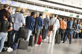 Air travellers stand in a queue in Terminal 1 of Frankfurt Airport in front of a check-in counter, Germany, Monday, June 15,…