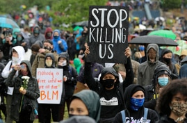 """A protester holds a sign that reads """"Stop Killing Us"""" during a """"Silent March"""" against racial inequality and police brutality…"""