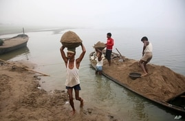 Laborers transport sand from boats to the shore after excavating the same from the bed of the River Yamuna in Allahabad, India,…