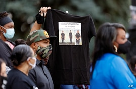 A supporter holds up a shirt to call attention to the death of Elijah McClain in August 2019 in Aurora, Colo., during a news…