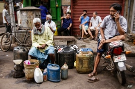 Ethnic Chinese Indians rest behind vendors selling their ware at a roadside market in Kolkata, India, Friday, June 19, 2020…
