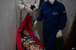 An emergency worker carries Jose Rocha on a hammock to a field hospital treating suspected COVID-19 patients in Manacapuru,…