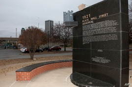FILE - In this Dec. 15, 2016 file photo, a memorial to Tulsa's Black Wall Street sits outside the Greenwood Cultural Center on…
