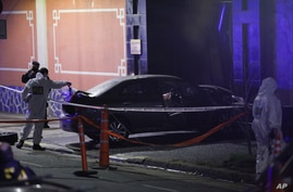 A police officer checks a car that crashed at the gate of the Chinese embassy in Buenos Aires, Argentina, Monday, June 22, 2020…