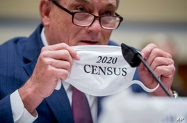 "Census Bureau Director Steven Dillingham holds up his mask with the words ""2020 Census"" as he testifies before a House…"