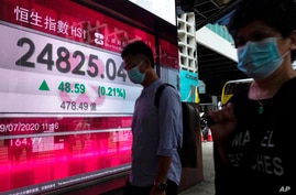 People wearing face masks walk past a bank's electronic board showing the Hong Kong share index in Hong Kong Wednesday, July 29…