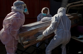 Funeral home workers in protective suits carry the coffin of a woman who died from COVID-19 into a hearse in Katlehong, near…