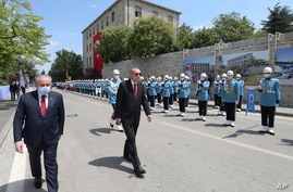 Turkey's President Recep Tayyip Erdogan, center, inspects a military honour guard as he arrives at the parliament for a…
