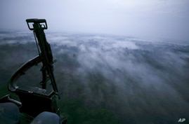 Seen from an Army helicopter, clouds cover the jungle of San Jose del Guaviare, Colombia, at dusk Friday, March 22, 2019…