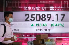 A man wearing a face mask walks past a bank's electronic board showing the Hong Kong share index at Hong Kong Stock Exchange…