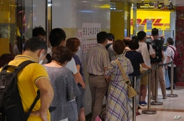 People queue up outside the DHL Express store in Hong Kong, Monday, June 1, 2020. Throngs of people lined up at DHL courier…
