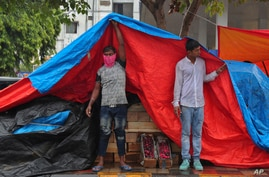 An Indian fruit vendor wearing face mask to protect from the coronavirus uses a plastic sheet to cover from rain in Hyderabad,…