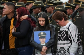 Relatives attend a ceremony marking one year since a car bomb attack on the police academy in Bogota, Colombia, Monday, Jan. 20…