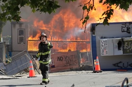 Construction buildings burn near the King County Juvenile Detention Center, Saturday, July 25, 2020, in Seattle, shortly after…