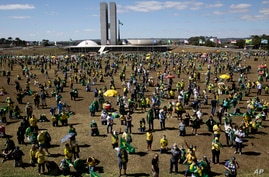 People show their support for Brazil's President Jair Bolsonaro, in Brasilia, Brazil, Sunday, July 19, 2020. Last week,…