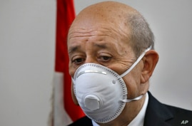 French Foreign Minister Jean-Yves Le Drian wears a mask to help prevent the spread of the coronavirus during his visit to the…
