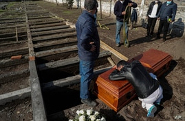 Peruvian migrant Jose Collantes grieves as he cries on the coffin that contains the remains of his wife Silvia Cano, who died…