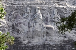 FILE - This June 23, 2015 file photo shows a carving depicting Confederate Civil War figures Stonewall Jackson, Robert E. Lee…