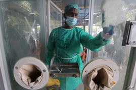 An employee cleans a booth at a testing and screening facility for the new coronavirus, in a hospital in Karachi, Pakistan,…