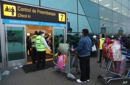 Passengers stand at a distance and wear masks amid the COVID-19 pandemic as they wait in line to check-in at the Jorge Chávez…