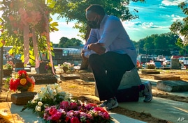 Will Boyd kneels at the grave of a family member who died after contracting the coronavirus, Saturday, June 20, 2020, in…