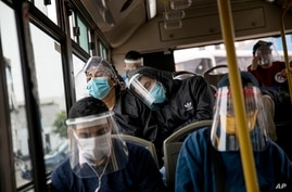 Commuters wearing protective face masks and face shields travel on a public bus in Lima, Peru, Wednesday, July 22, 2020. Peru…