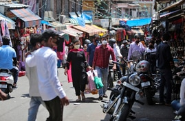 Indians wearing a mask as a precaution against the coronavirus shop at a market in Jammu, India, Sunday, July 5, 2020. India's…