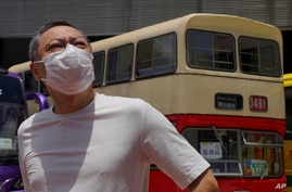 Occupy Central leader Benny Tai stands in front of a vintage double-deck bus used as a polling center for an unofficial …