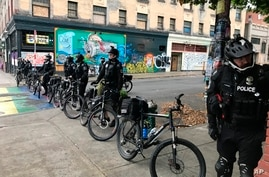 Seattle police block a street with their bicycles in the Capitol Hill Organized Protest zone early Wednesday, July 1, 2020…