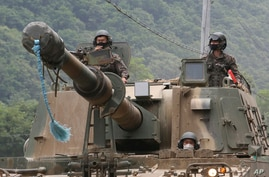 South Korean army soldiers ride a K-9 self-propelled howitzer during the annual exercise in Paju, South Korea, near the border…