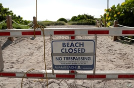 A sign is posted at a closed entrance to the beach during the new coronavirus pandemic, Friday, July 3, 2020, in the South…