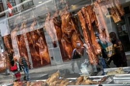 Pedestrians are reflected in the storefront window of a Chinese restaurant displaying roasted duck in downtown Lima, Peru,…