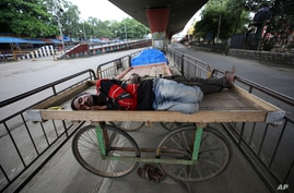 Homeless men sleep on a handcart parked on a road divider in a containment zone during lockdown in Bengaluru, India, Sunday,…