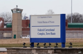 FILE - In this Dec. 10, 2019, file photo the guard tower flanks the sign at the entrance to the U.S. Penitentiary in Terre…