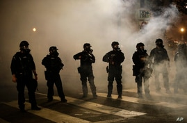 Federal officers are surrounded by smoke as they push back demonstrators during a Black Lives Matter protest at the Mark O…